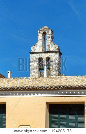 Old building apartments roof bells in ramshackle condition. Sky background. Greece, Corfu island