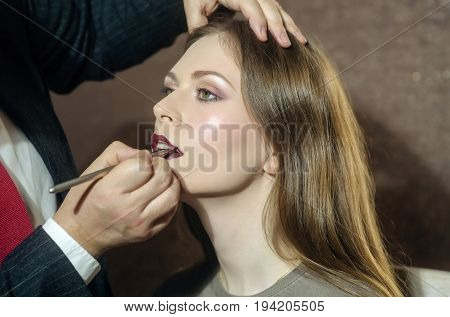 Woman Getting Lips Painted In Beauty Salon