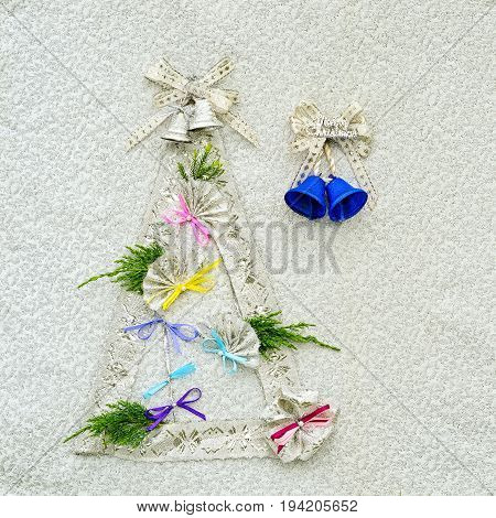 new year and christmas background with xmas tree silhouette made from silver ribbons bells and flamenco fans as decorations.