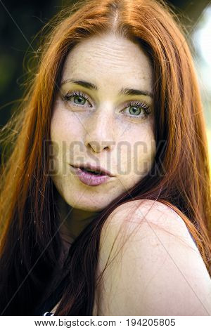 Beautiful woman with red hair. Smiling redhead during summer in sunny weather. Close up, working in nature, outdoor office, lifestyle.
