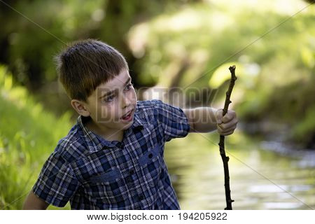 Little boy wanders through small stream and he is supported by wooden stick. Child wades through rivulet. Humorous, funny and happy summer sunny scene with son and brook.