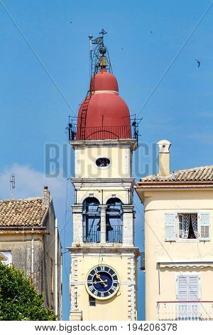Old Byzantine clock tower on city background. Greece, Corfu
