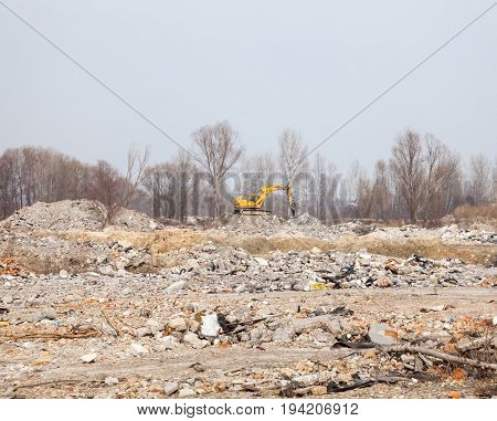 Yellow excavator working on the city landfill