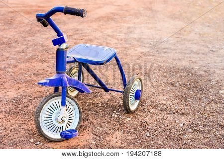 concept memory, blue tricycle bike on gravel background