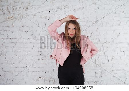 Beautiful young woman on leather jacket. Fashion model in pink leather jacket. Posing near white brick wall. studio shots.