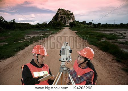 Surveyor or Engineer making measure by Theodolite with partner on the field.