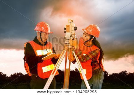 Surveyor or Engineer making measure by Theodolite with partner on the field and colorful sky background.