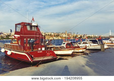 ISTANBUL TURKEY - MAY 1 2017: Fishing boats at the pier with Halic metro bridge and Galata tower on background