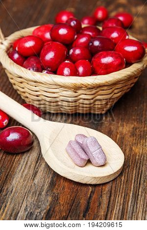 cranberries pills and fresh cranberries on an old kitchen table