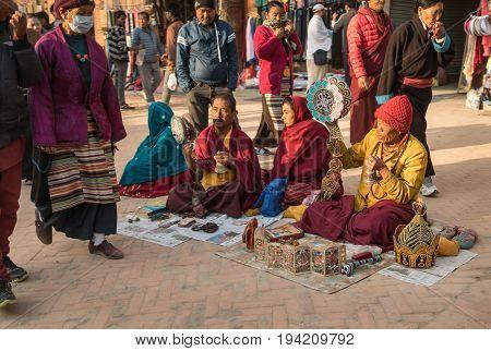 The Tibetan pilgrims sing traditional Buddhist songs - puja accompanied by ritual drums sitting on the sidewalk at a stupa Bodnath on March 7 2017 Katmandu Nepal.