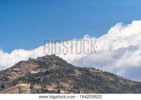Many paragliders flyinf over the mountain Sarangkot in the Himalayas against the background of clouds.