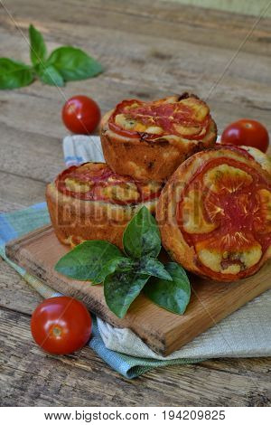 Salty Snack. Homemade Muffins With Cheese, Tomatoes And Basil On Wooden Background. Savory Pastry.