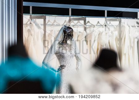 The mannequin looking as liquid terminator in a beautiful wedding attire of the bride shining the polished metal.