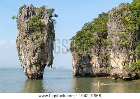 Phang Nga Bay Thailand - 1 February 2010: Man driving his boat out of Phang Nga Bay bay in Thailand
