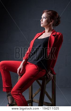 Beautiful brown haired woman in nice red pantsuit sitting on the wooden chair studio portrait
