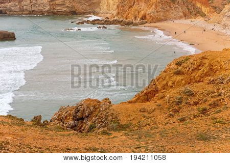 People at the beach of Sagres. This beach is a part of famous tourist region of Algarve.