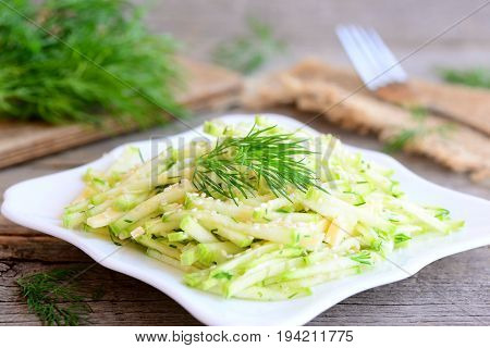 Zucchini courgette salad with cheese. Homemade salad with raw zucchini courgette slices, cheese slices and chopped dill on a plate. Simple and delicious vegetable summer salad. Rustic style. Closeup