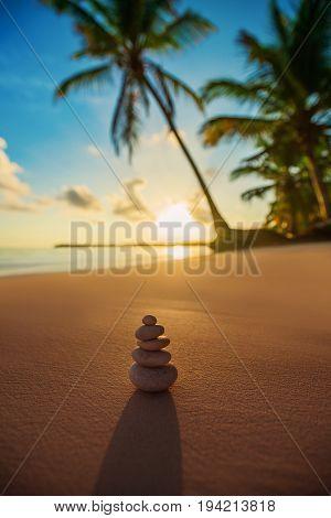 Stones balance on beach tropical sunrise shot