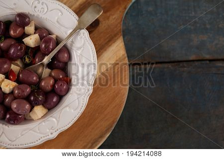 Cropped image of black olives served in plate on tray at table