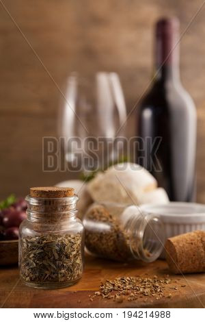 Close up of spices in mason jars on table with wine bottle in background