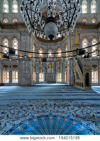 Istanbul, Turkey - April 20, 2017: Interior shot of Nuruosmaniye Mosque, an Ottoman Baroque mosque, overlooking niche (Mihrab) and marble minbar (Platform) with many colored stained glass windows