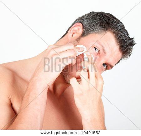 Man in bathroom claening face skin with batting cotton pads