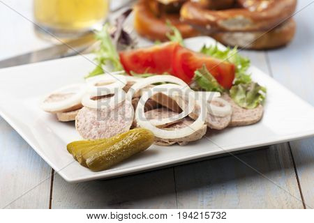 bavarian sausage salad with a pretzel on wood