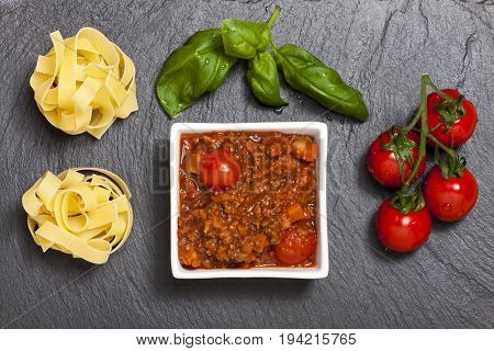 overview of tagliatelle bolognaise with basil on slate