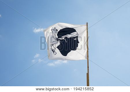 corsican flag on a sunny day with a cloud
