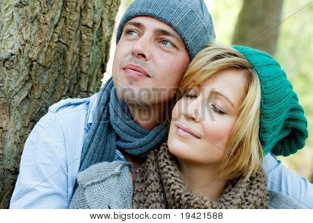Embracing sitting young couple drinking tea outside in park enjoying landscape vacation in cold spring season with picknick