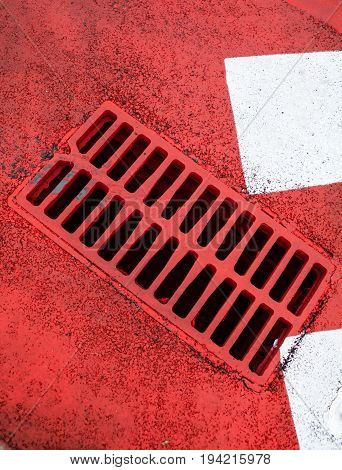Drain grate on the road with red and white road marking.