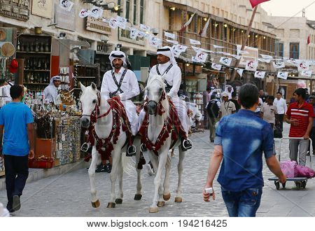 DOHA, QATAR - JULY 6, 2017: Mounted police pass under bunting expressing loyalty to Qatari Emir Sheikh Tamim bin Hamad in Doha's Souq Waqif market during the diplomatic crisis with neighbouring states