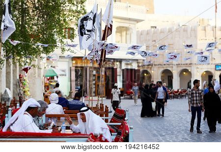 DOHA, QATAR - JULY 6, 2017: Flags and bunting with the image of  Qatari Emir Sheikh Tamim in the capital's Souq Waqif demonstrate  unity during the diplomatic crisis with neighbouring Arab states