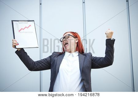 Business Concept Of Success And Growth. A Successful Woman Boss, In A Suit And Wearing Glasses, Hold