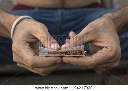 Close-up photograph of a man's hands rolling a joint