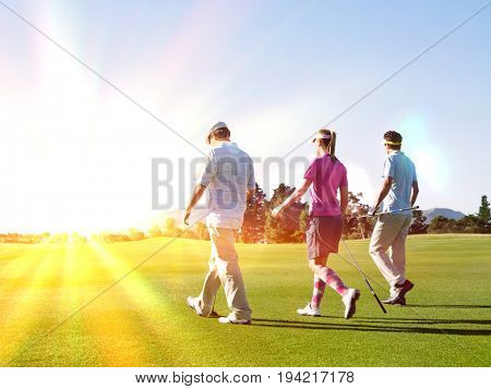Rear view of three young golfers walking on golf course