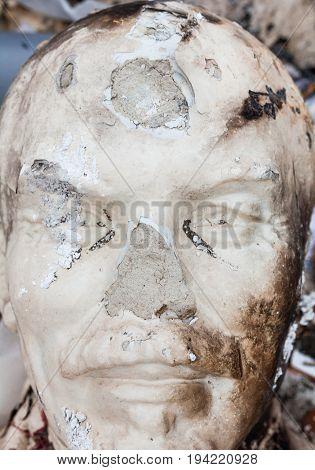 Decommunization in Ukraine. Damaged bust of Lenin in the garbage dump. Close-up.