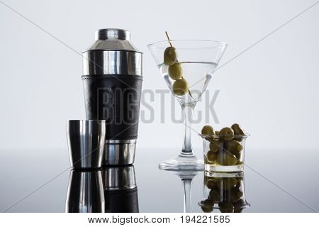 Close-up of cocktail martini with olives and shaker on table against white background