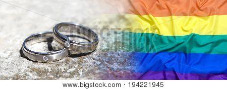 Wedding rings with rainbow flag on a stone