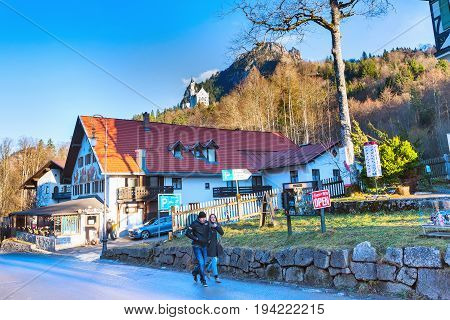 Fussen, Germany - December 27, 2016: Beautiful painted of traditional bavarian house and Neuschwanstein castle in German alps in Bavaria