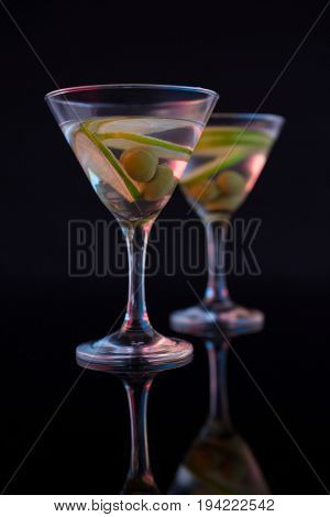 Close-up of cocktail martini with olives and lime on table against black background