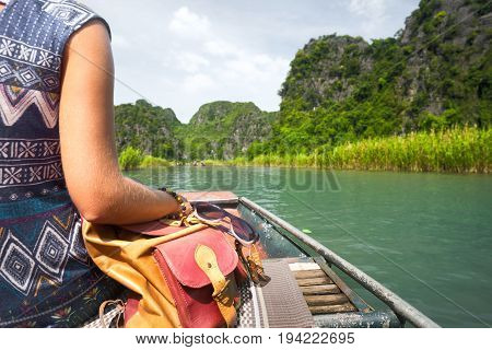 Woman in dress with backpack sitting in boat enjoying river and valley view. Mountains landscape travel to Asia happiness emotion summer hike concept.