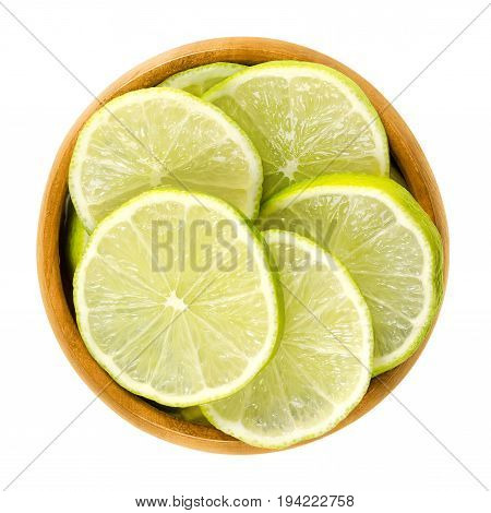 Lime slices in wooden bowl. Fresh cut unripe green edible citrus fruit discs. Key lime, Citrus aurantiifolia. Isolated macro food photo close up from above on white background.