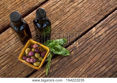 Close-up of pickled olives with herbs and balsamic vinegar bottles on table