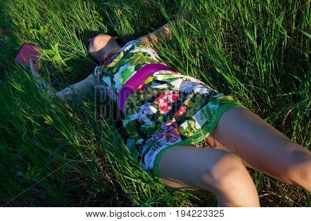 Sexy woman with a book lying in the grass.