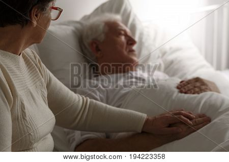 Sad senior man in hospital bed and his wife sitting next to him