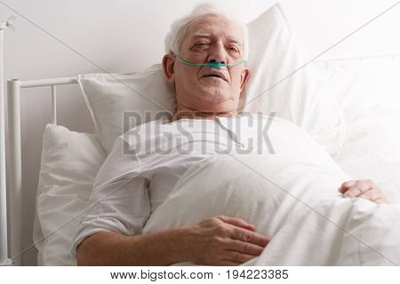 Sick senior man laying in hospital bed
