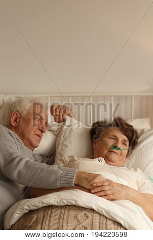 Worried husband laying next to his sick wife on hospital bed
