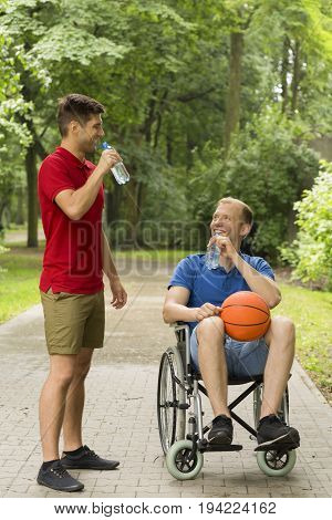 Disabled man on wheelchair and his friend drinking water after basketball game in the park