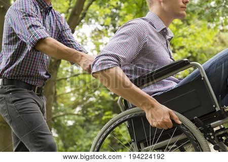 Shot of a man pushing his friend in wheelchair